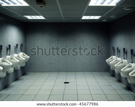 men's public toilet with urinals on both sides - stock photo