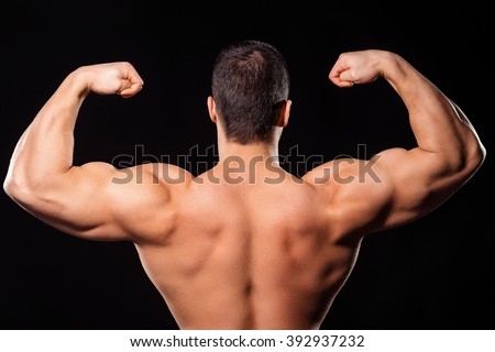 Men's rear double biceps pose. Bodybuilder's rear double biceps pose. Upper back and arms. So close to winning. - stock photo