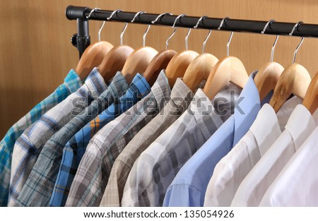 Men's shirts on hangers in wardrobe