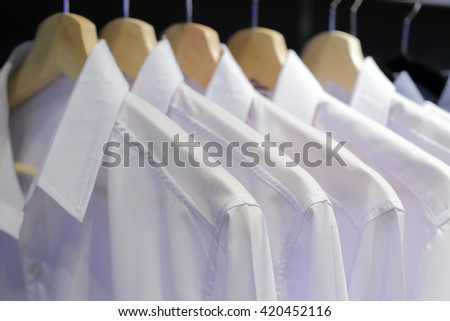 Men's shirts on hangers in wardrobe - stock photo
