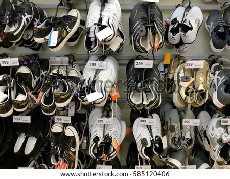 Men's shoes on supermarket's shelves and their price tags with Baht currency Hua Hin, Thailand February 10, 2017