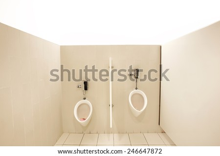 Men's urinals in well lit restroom with tiled floor - stock photo