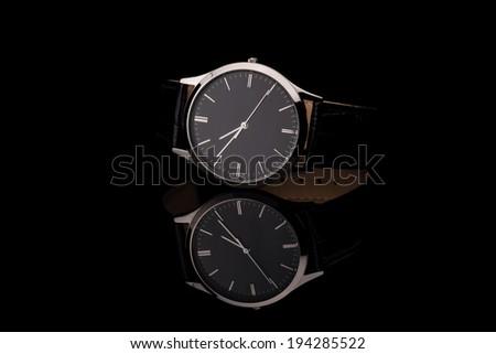 Men's wrist watch on black background. Studio shoot. - stock photo