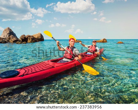 Men sailing kayaking on the clear water of the sea. - stock photo
