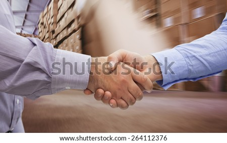 Men shaking hands against worker with fork pallet truck stacker in warehouse - stock photo