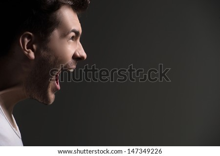 Men shouting. Side view of men shouting while isolated on grey - stock photo