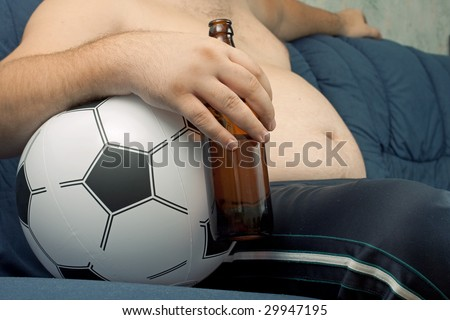 Men sitting on the sofa with a bottle of beer. - stock photo