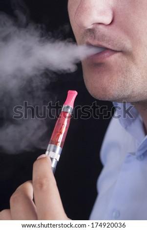 Men smoke an electronic cigarette - stock photo