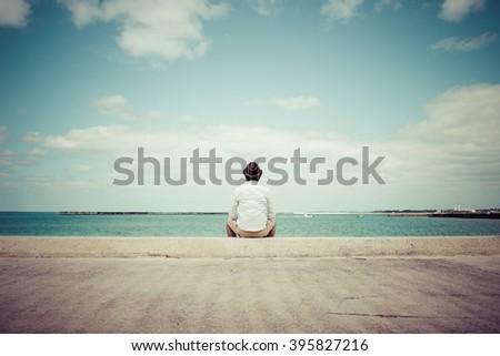 Men stare at the sea - stock photo
