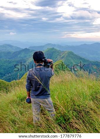 Men survey at the top of  (Khao Chang Puak) mountains in Thailand. - stock photo