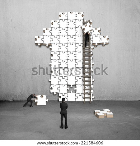 men teamwork for puzzles in arrow shape on concrete wall - stock photo