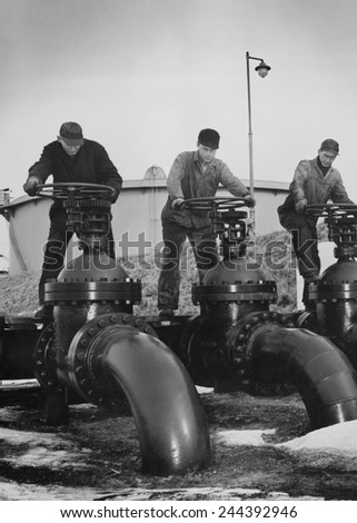 Men turn the wheels of large valves that regulate the flow of oil into oil tankers at a U.S. Atlantic coast seaport. Ca. 1944. - stock photo