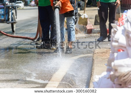 men use water cleaning the street and correct rubbish - stock photo