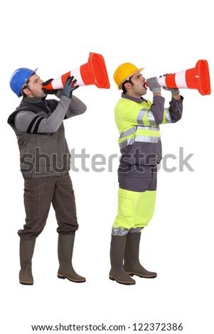 Men using traffic cones as loudspeakers - stock photo