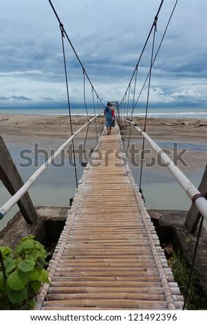 Men walking on suspension bridge over small river leading to the sea in Bali. - stock photo