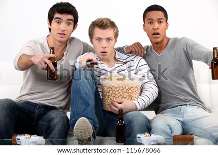 Men watching a horror movie - stock photo