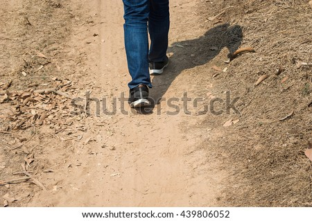 Men wear jeans and wear walking shoes on the ground. - stock photo