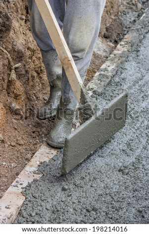 men wearing rubber boots submerged in poured concrete at the building site. selective focus. - stock photo