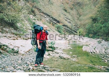 Men with a backpack standing on the river bank