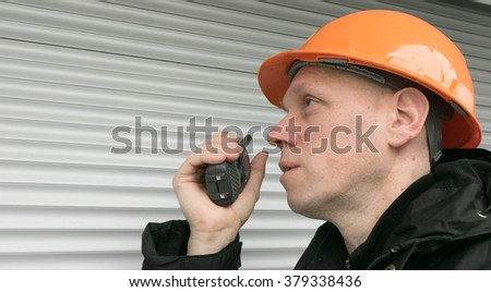 Men with a Walkie-Talkie and a Helmet - stock photo