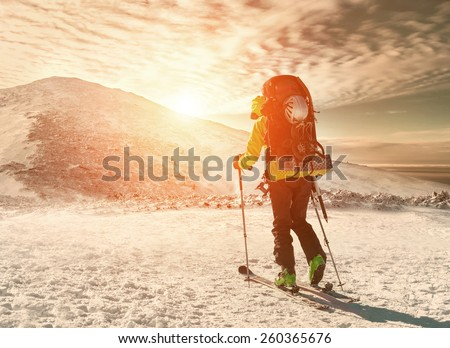 Men with backpack at ski goes to the top of mountain in sun day - stock photo