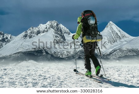 Men with backpack at ski goes to the top of mountain in sun day