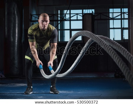 Men with battle rope battle ropes exercise in the fitness gym. CrossFit.