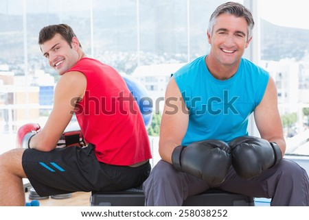 Men with box gloves smiling at camera in fitness studio - stock photo