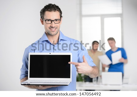 Men with laptop. Happy young businessman holding a laptop and pointing it while colleagues working on the background - stock photo