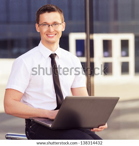 men with laptop  on background modern building