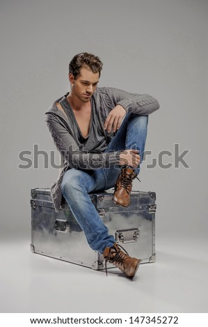 Men with mysterious box. Thoughtful young men sitting on the metal box and looking down while isolated on grey - stock photo