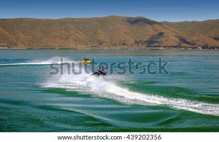 men with sea scooter, water jet rider, jet skiing on lake Sevan in Armenia - stock photo