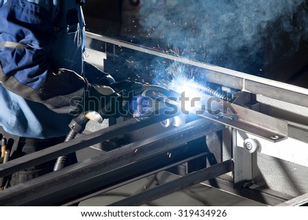 men worker welding at the industrial factory - stock photo