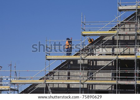 Men working at the new construction site with blue sky on background. - stock photo