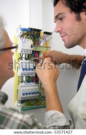 Men working on a circuit breaker - stock photo