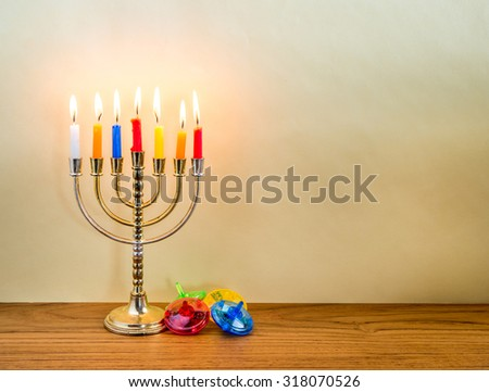 Menorah with candles and colorful  dreidels for Hanukkah celebration. - stock photo
