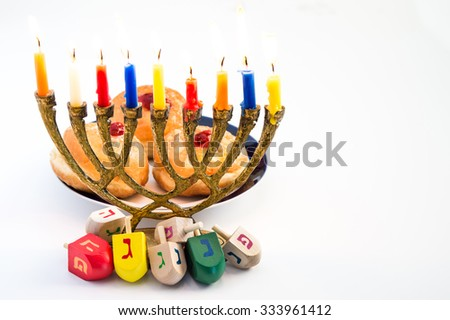 Menorah with candles, donuts with jelly and wood dreidels with Hebrew caps letters for Hanukkah celebration. - stock photo