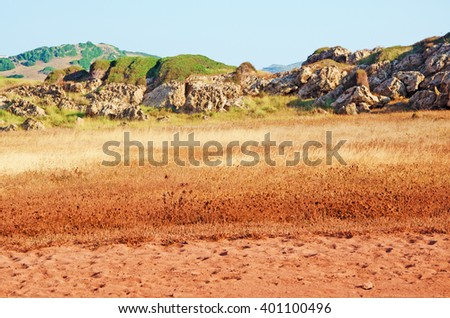 Menorca, Balearic Islands, Spain: the red sand on the path to Cala Pregonda beach on July 15, 2013. Cala Pregonda is a secluded cove with rocks and red sand: its beach looks like the planet of Mars
