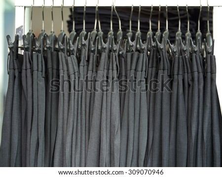 Mens dress pants trousers hanging in a retail shop - stock photo