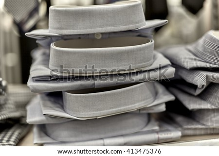 Mens dress shirts stacked on shelf in department store with neckties in the background with shallow depth of field - stock photo
