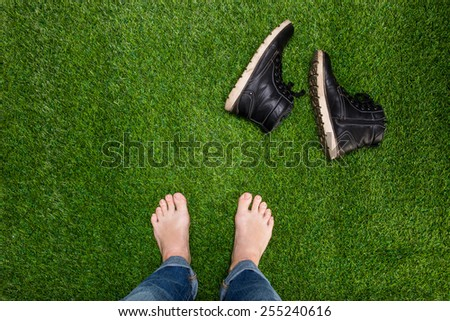 Mens feet resting on green grass with lying boots