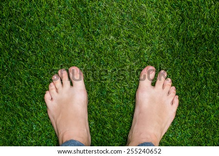 Mens feet standing on grass close up - stock photo