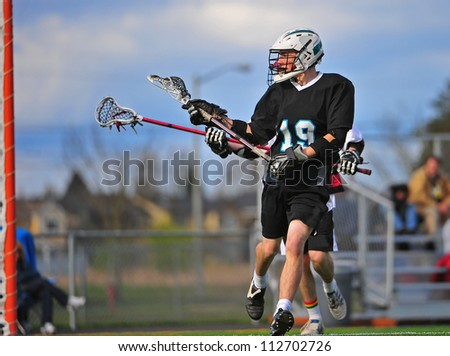 Mens lacrosse player taking a shot on the goal with the defender close behind him. - stock photo