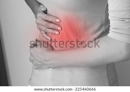 menstruation pain or stomach ache, hand holding belly closeup - stock photo