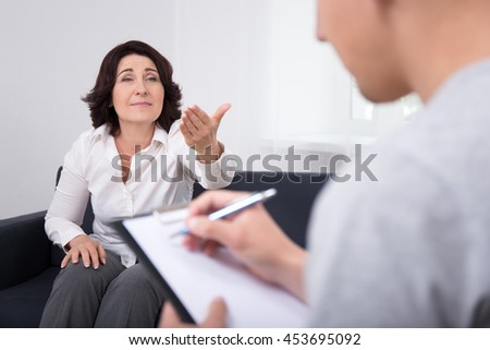 mental health concept - sad mature woman talking about her problems with psychotherapist or psychologist - stock photo