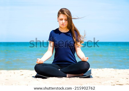 Mental health. Young woman practicing yoga at sea.  - stock photo