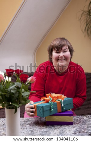 Mentally defective woman holding many gifts - stock photo