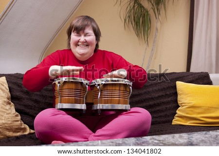 Mentally disabled woman enjoys her music therapy - stock photo
