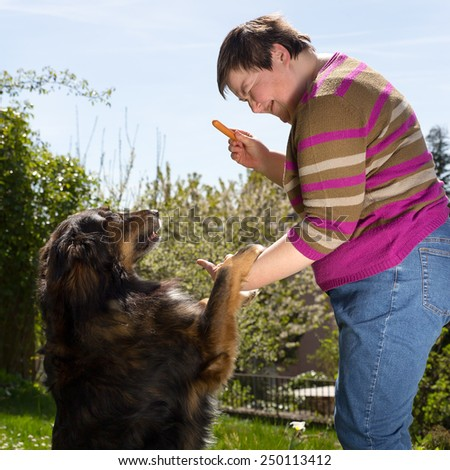 mentally disabled woman is feeding a dog - stock photo