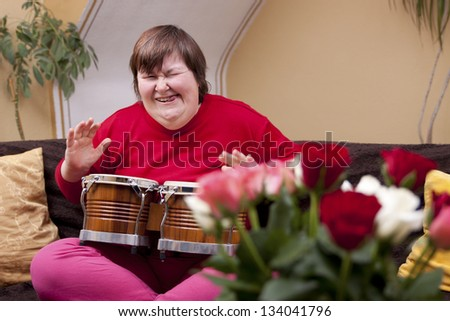 Mentally disabled woman plays drums - stock photo